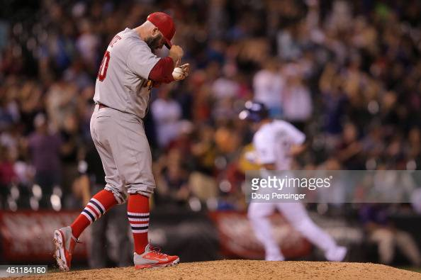 Relief pitcher Jason Motte of the St Louis Cardinals returns to the mound as Drew Stubbs of the Colorado Rockies rounds the bases on his pinch hit...