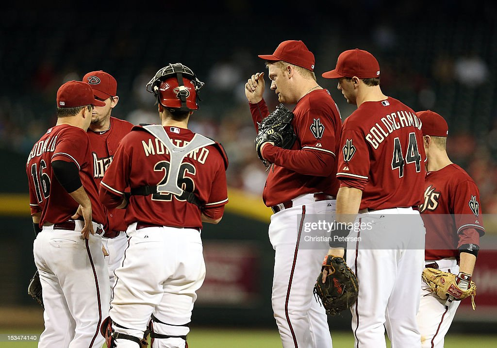 Relief pitcher <a gi-track='captionPersonalityLinkClicked' href=/galleries/search?phrase=J.J.+Putz&family=editorial&specificpeople=243125 ng-click='$event.stopPropagation()'>J.J. Putz</a> #40 of the Arizona Diamondbacks talks with teammates on the mound during the MLB game against the Colorado Rockies at Chase Field on October 3, 2012 in Phoenix, Arizona.