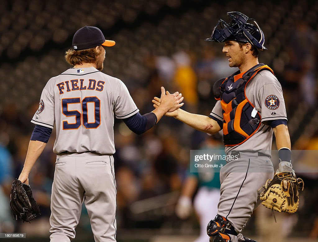 Relief pitcher Josh Fields #50 of the Houston Astros is congratulated by catcher Cody Clark #39 after defeating the Seattle Mariners 6-3 at Safeco Field on September 9, 2013 in Seattle, Washington.