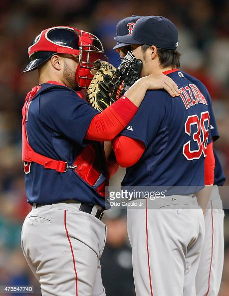 Relief pitcher Junichi Tazawa of the Boston Red Sox gets a visit from catcher Sandy Leon against the Seattle Mariners in the ninth inning at Safeco...