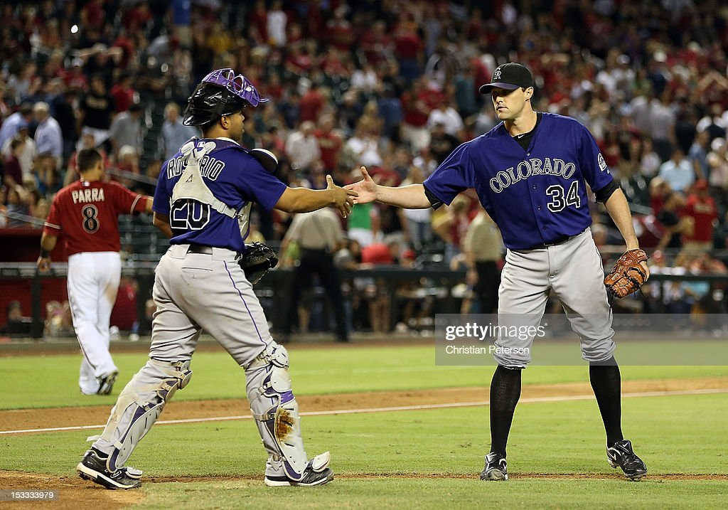 Relief pitcher Matt Belisle #34 of the Colorado Rockies celebrates with catcher Wilin Rosario #20 after defeating the Arizona Diamondbacks 2-1 in the MLB game at Chase Field on October 3, 2012 in Phoenix, Arizona.