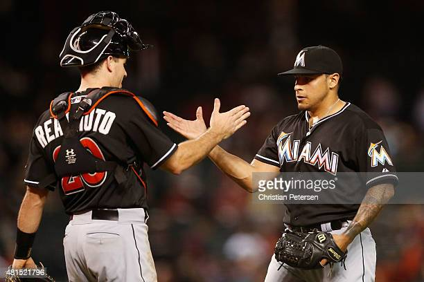 Relief pitcher Miguel Rojas of the Miami Marlins highfives catcher JT Realmuto after defeating the Arizona Diamondbacks 30 in the MLB game at Chase...