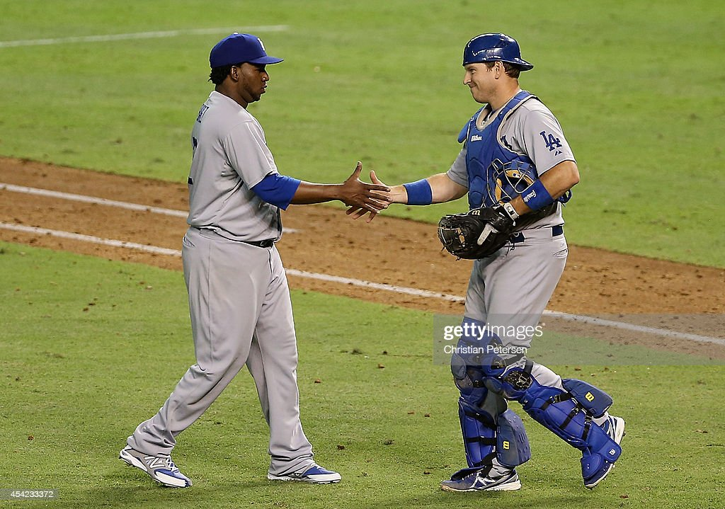 Relief pitcher Pedro Baez #52 of the Los Angeles Dodgers celebrates with catcher A.J. Ellis #17 after defeating the Arizona Diamondbacks in the MLB game at Chase Field on August 26, 2014 in Phoenix, Arizona. The Dodgers defeated the Diamondbacks 9-5.