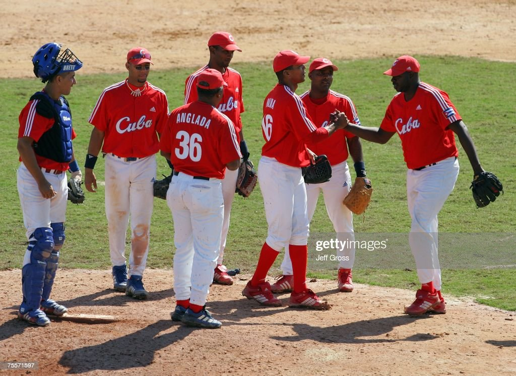 Relief pitcher Pedro Luis Lazo (R) #99 of Cuba replaces and congratultes starting pitcher Adiel Palma #16 in the eighth inning of the Baseball Final against the USA during the 2007 Pan American Games at the City of Rock on July 20, 2007 in Rio de Janeiro, Brazil. Cuba defeated the USA