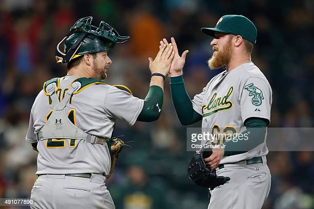 Relief pitcher Sean Doolittle of the Oakland Athletics is congratulated by catcher Stephen Vogt after defeating the Seattle Mariners 42 at Safeco...