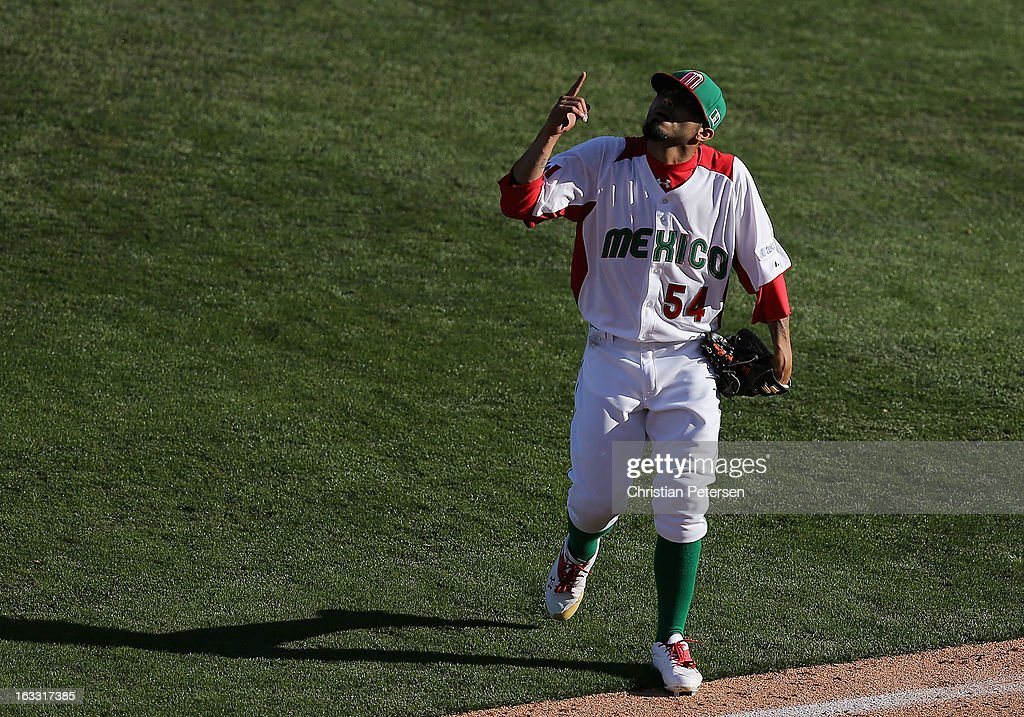 Relief pitcher <a gi-track='captionPersonalityLinkClicked' href=/galleries/search?phrase=Sergio+Romo&family=editorial&specificpeople=5433590 ng-click='$event.stopPropagation()'>Sergio Romo</a> #54 of Mexico points up to the sky as he walks off the field during the ninth inning of the World Baseball Classic First Round Group D game against Italy at Salt River Fields at Talking Stick on March 7, 2013 in Scottsdale, Arizona. Italy defeated Mexico 6-5.