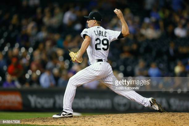 Relief pitcher Shane Carle of the Colorado Rockies delivers to home plate during the eighth inning against the San Francisco Giants at Coors Field on...