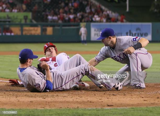 Relief pitcher Tanner Scheppers of the Texas Rangers lies in the path of Mike Trout of the Los Angeles Angels of Anaheim who slides safely into home...