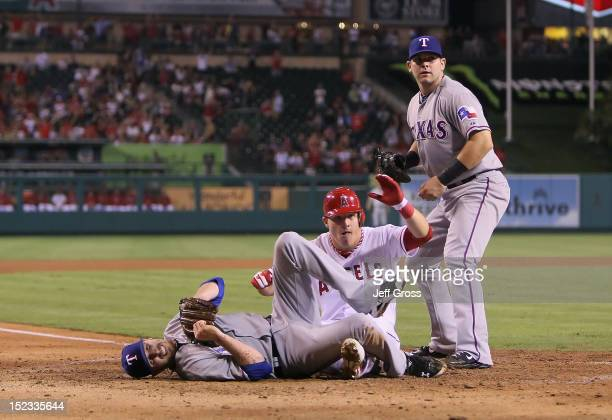 Relief pitcher Tanner Scheppers of the Texas Rangers winces in pain as Mike Trout of the Los Angeles Angels of Anaheim slides safely into home past...