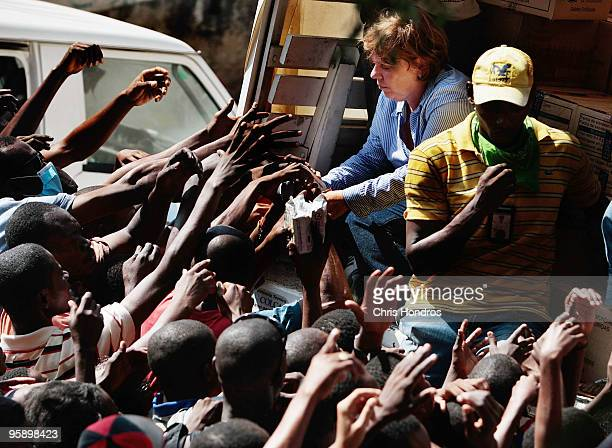 Relief workers hand out emergency rations from the World Food Program off of the back of a truck January 20 2010 in PortauPrince Haiti Aid has...