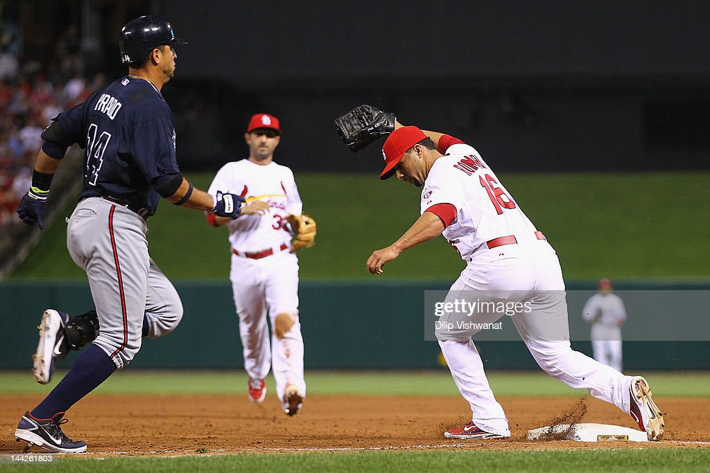 Reliever JC Romero of the St Louis Cardinals beats Martin Prado of the Atlanta Braves to first base for an out at Busch Stadium on May 12 2012 in St...
