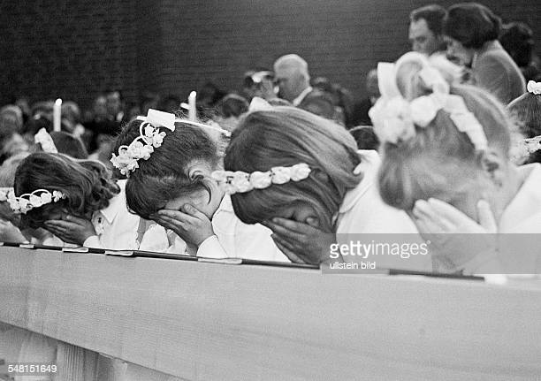 religion Christianity First Communion four girls pray in the pew after receiving the Holy Communion aged 8 to 12 years Babette
