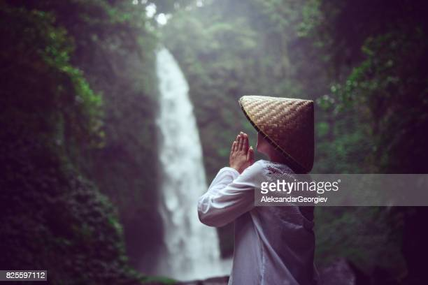 Religious Asian Female Praying by the Rainforest Waterfall