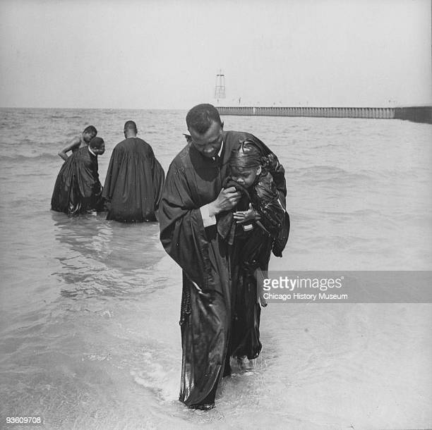 A religious ceremony possibly a baptism is held at Chicago's 31st Street beach ca1950s Image shows a man holding a young child in his arms while...