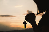 Religious concepts. Silhouette of a girl holding a crucifix to God. Morning with beautiful sunrise, Symbol of Faith. Christian life prayer crisis to god.