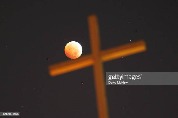 A religious cross is seen as the moon is illuminated by sunlight reflected off the Earth during a total lunar eclipse one of four socalled 'blood...