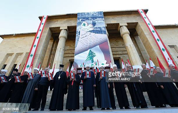 Religious figures hold national flags during a rally organised by the Joy of Giving NGO to mark the 41st anniversary of the Lebanese civil war on...