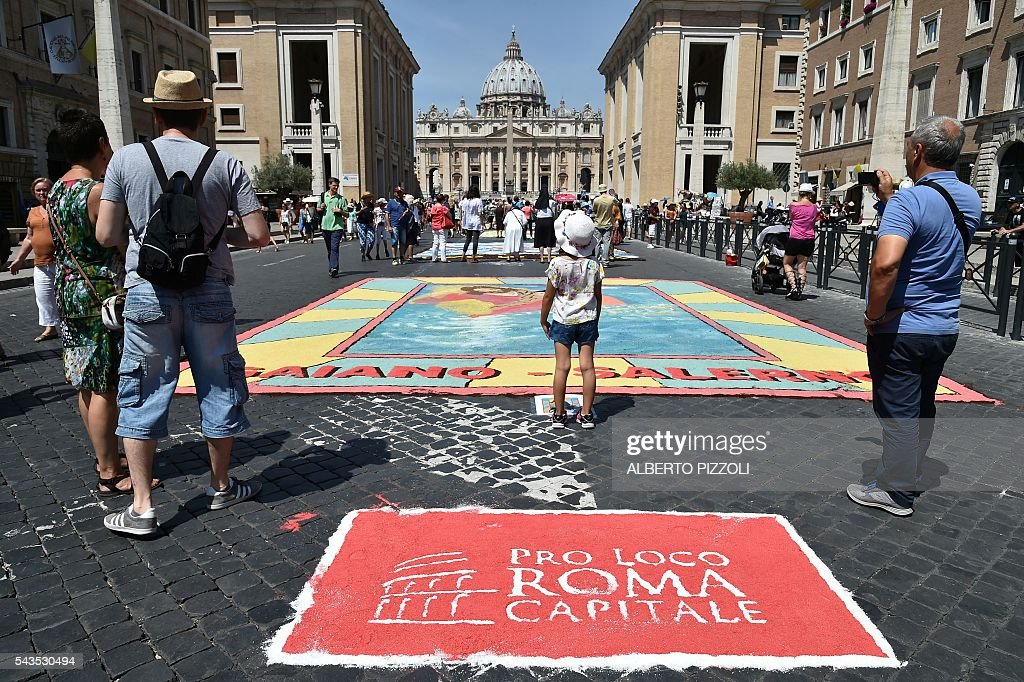 Religious frescoes are drawn on the Via della Conciliazione near the Vatican on the occasion of the feast of Saints Peter and Paul, patrons of Rome, on June 29, 2016 in Rome. / AFP / ALBERTO