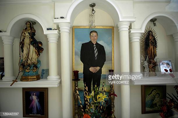Religious images flank a picture of the deceased buried in a mausoleum of the 'Humaya Gardens' cementery on July 13 2011 in Culiacan Sinaloa state...