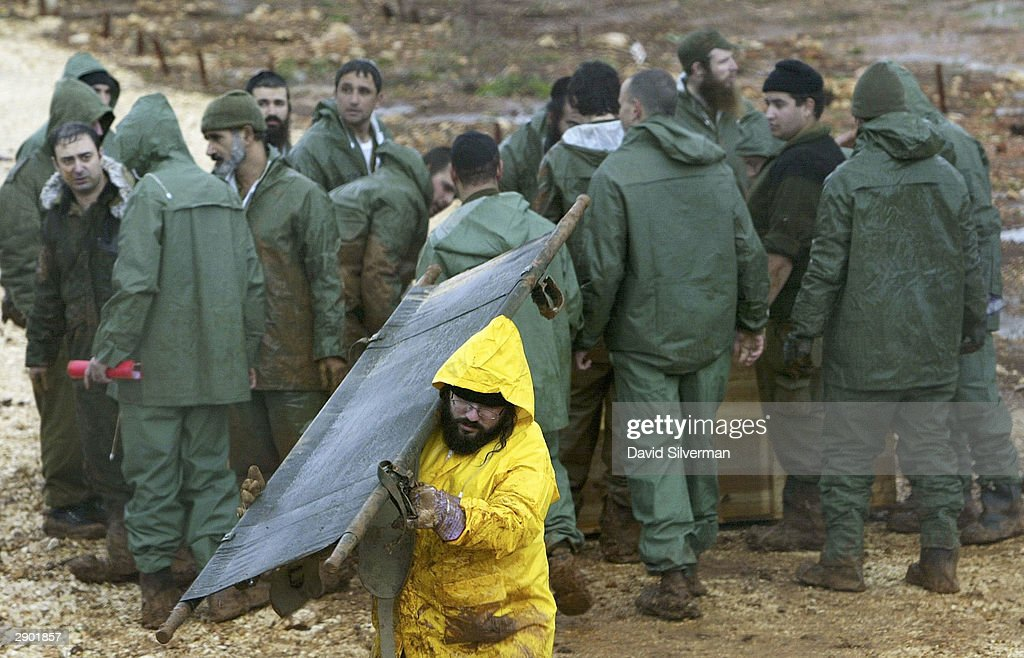 A religious Israeli soldier carries an empty stretcher as others gather round the body of one of 59 Lebanese exhumed from the army's Enemy Graveyard...