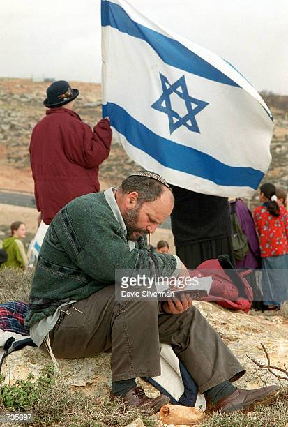 A religious Jew reads his prayer book as settlers take over a hilltop overlooking the Ramallah bypass road January 4 a highway which was built to...