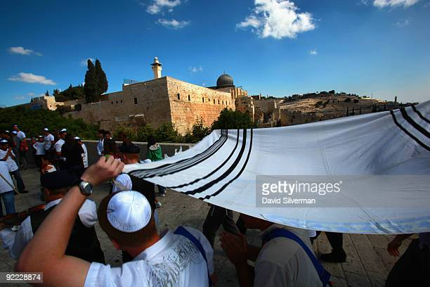 A religious Jewish family escorts their 13yearold son under a Tallit past alAqsa mosque to his Barmitzvah ceremony at the Western Wall Judaism's...