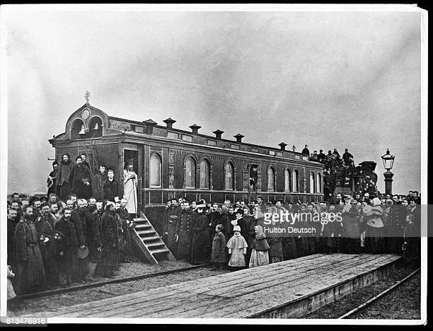 A religious leader stands in the doorway of a railroad car surrounded by a crowd of people during a religious service in Manchuria