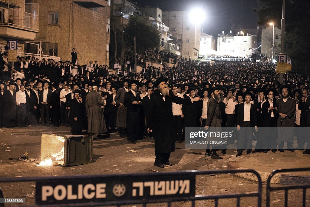 A religious leader (C) tries to calm the crowd as thousands Ultra Orthodox Jews clash with Israeli police forces in Jerusalem on May 16, 2013 during a protest in front of the main army recruitment office to demonstrate against any plans to make them undergo military service, a police spokesman said. Protesters also prayed and chanted 'the Torah above everything!' referring to Jewish religious law, and 'the army will not take yeshiva (religious seminary) pupils.'