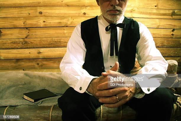 Religieux dans une cabine en bois homme assis sur un lit de Prier