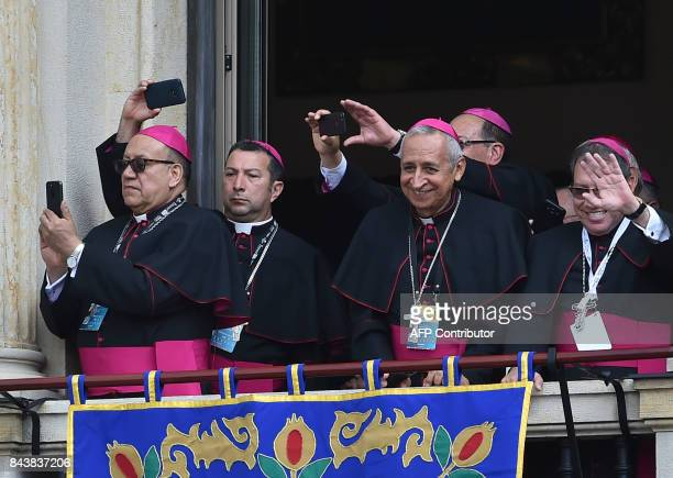 Religious men take pictures and wave goodbye as Pope Francis leaves the Archbishop's Palace at Bolivar Square in Bogota on September 7 2017 Pope...