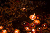 Religious offering to holy Ganges river after sunset. As an offering, diya or oil lamps are put on small boats made of leaves and set afloat on the water.