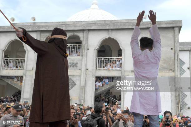 A religious officer canes an Acehnese man for spending time in close proximity with a woman who is not his wife which is against Sharia law in Banda...