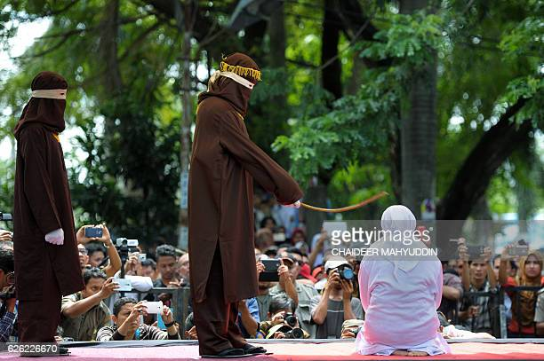 A religious officer canes an Acehnese woman 100 times for having sex outside marriage which is against Sharia law in Banda Aceh on November 28 2016...