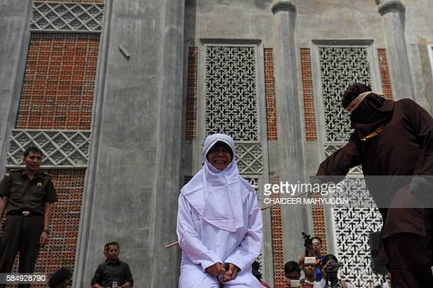 TOPSHOT A religious officer canes an Acehnese youth onstage as punishment for dating outside of marriage which is against sharia law outside a mosque...