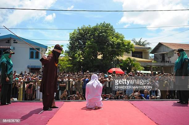 A religious officer canes an Acehnese youth onstage as punishment for dating outside of marriage which is against sharia law outside a mosque in...