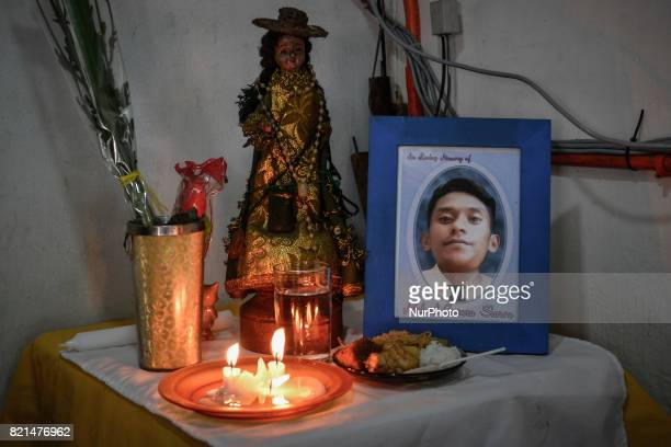 A religious statue candles and food are left next to a picture of Michael Siaron who was killed a year ago by unknown assailants in Pasay Metro...