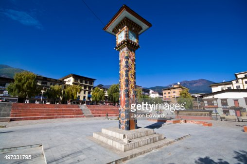 Religious symbols carved into the walls of a clock tower in a Himalayan town square.