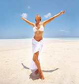 Full-length of a happy young woman enjoying her vacation on a white beach