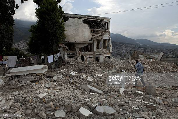 Remains of a hotel that collapsed during the earthquake February 2011 in PortauPrince Haiti Men look for scrap metal in the remains as a source of...