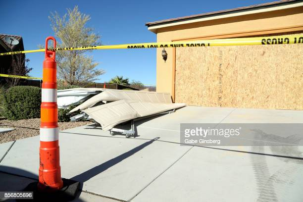 Remains of the garage door sit in the driveway in front of the house in the Sun City Mesquite community where suspected Las Vegas gunman Stephen...