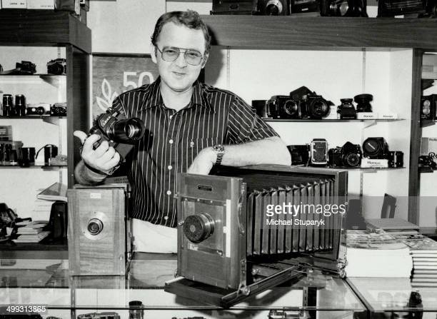 Remember when Shop owner Erik Olesen displays a couple of vintage portrait cameras from his antique collection while holding one of the latest models...