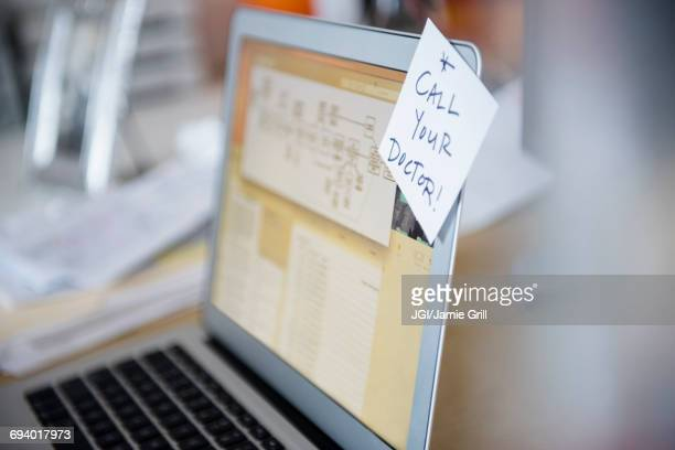 Reminder on adhesive note attached to laptop