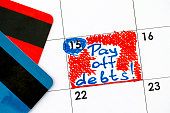 Reminder Pay off Debts! in calendar with credit cards. Close-up.