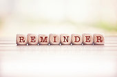 Reminder word written on cube wooden blocks. Defocused background.