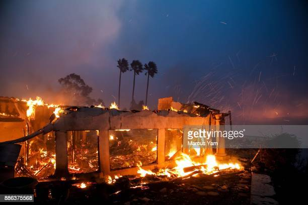 Remnants of a burned down a home as a brush fire continues to threaten other homes on December 5 2017 in Ventura California