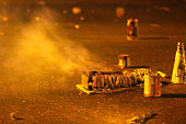 Remnants of burnt pyrotechnics lie on the road at night on New Year's Eve. The fireworks are still smoking