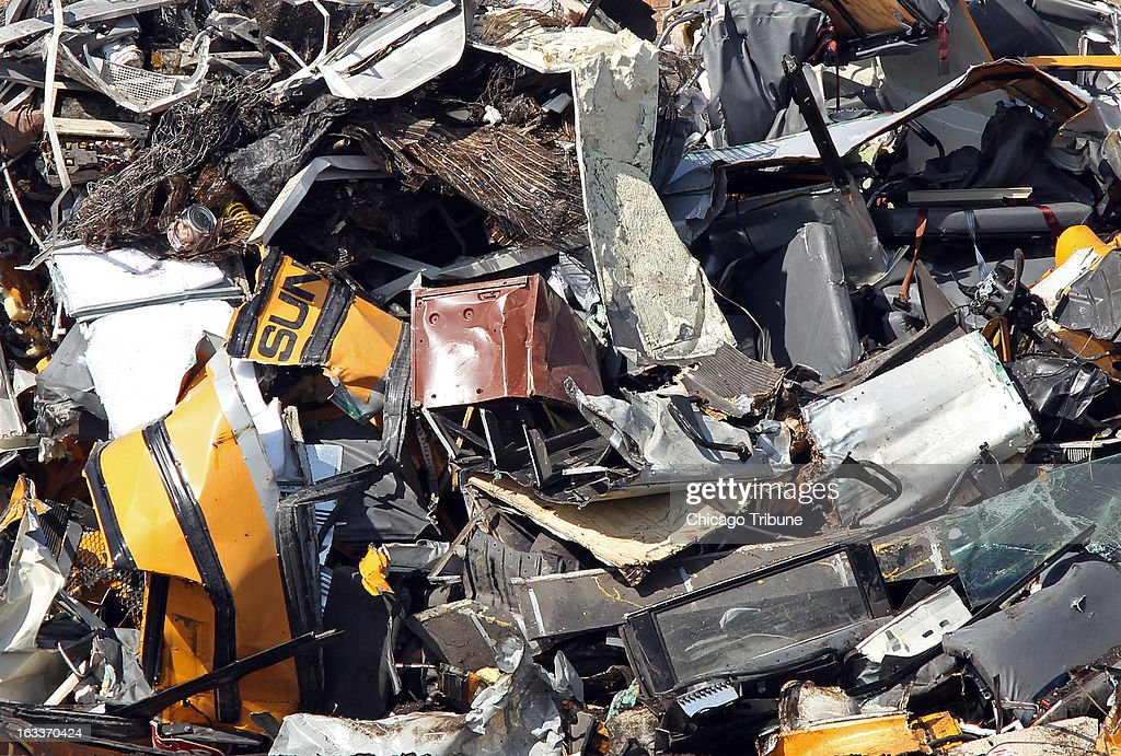 Remnants of crumpled school buses are piled amid a heap of scrap metal at SRV Metal Scrapper, Friday, March 8, 2013, in Chicago, Illinois. Buses were reported missing by Sunrise Transportation Thursday night.