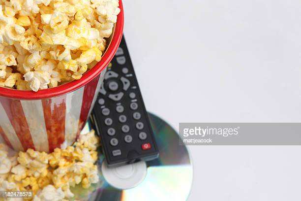 DVD, remote control, and popcorn sitting on gray background.