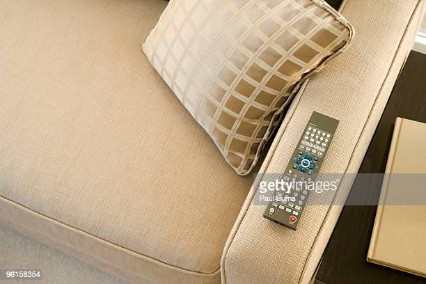 A TV remote control on the armrest of sofa