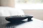 "Close up of the remote control of a smart TV in the night table of a bedroom ""n"